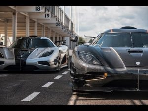 Two Koenigsegg One:1s, one black and one silver with a white stripe, are driving down a city road.