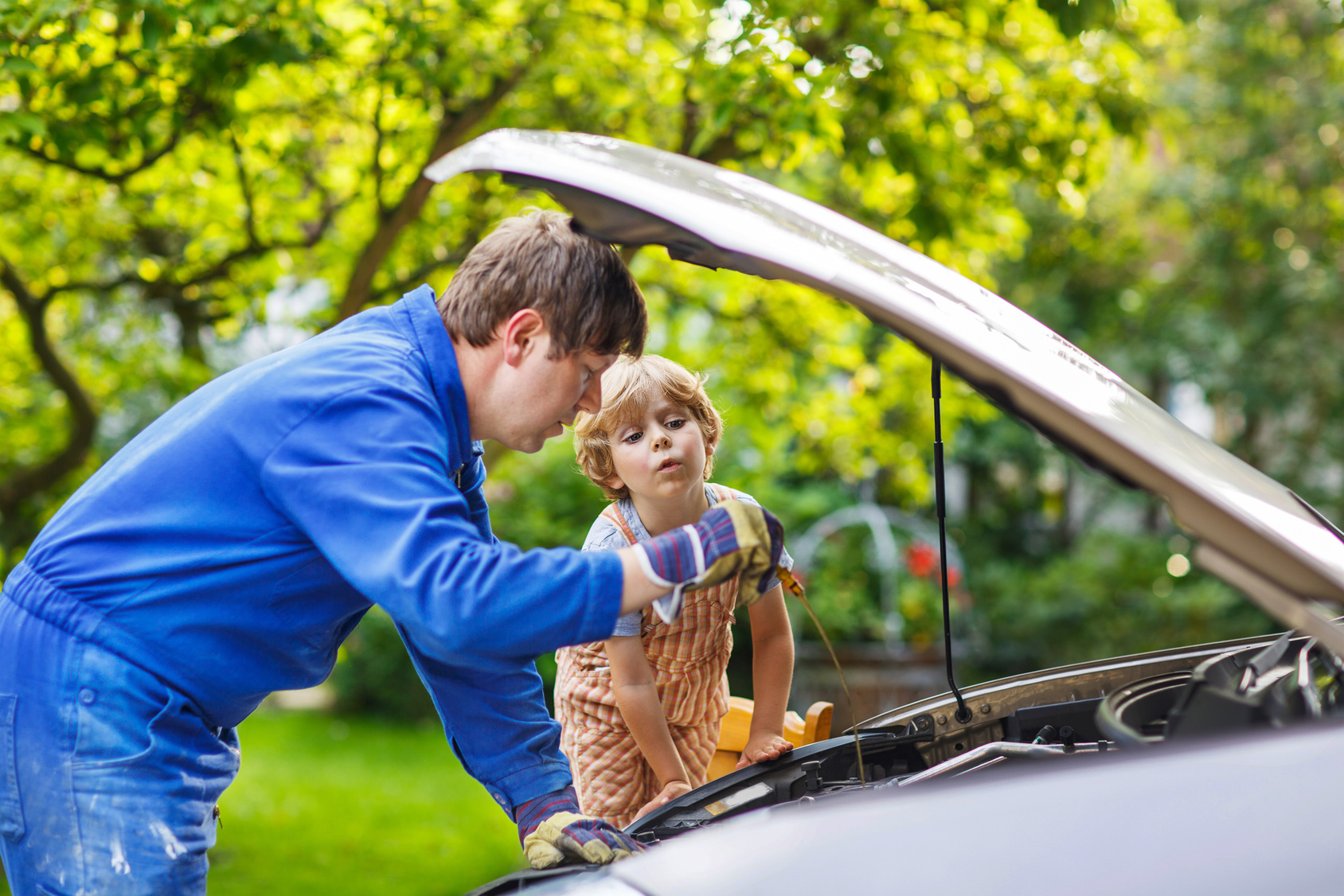 Father teaching son car care